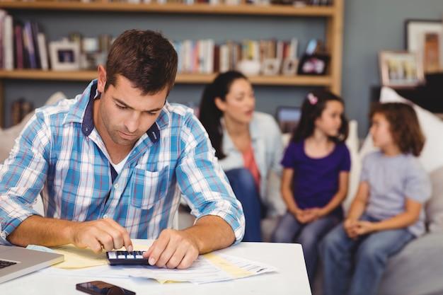 Uomo serio che per mezzo del calcolatore mentre seduta della famiglia