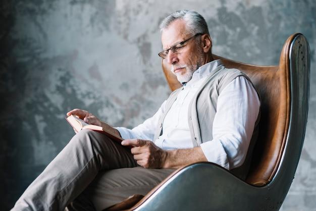 Uomo serio che si siede sul libro di lettura della sedia contro il muro di cemento