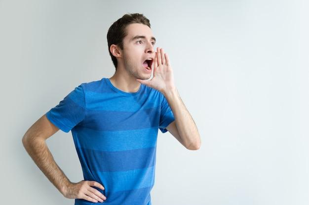 Uomo serio che tiene la mano vicino alla bocca e che grida forte