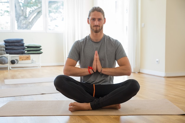Uomo serio che tiene le mani insieme a lezione di yoga