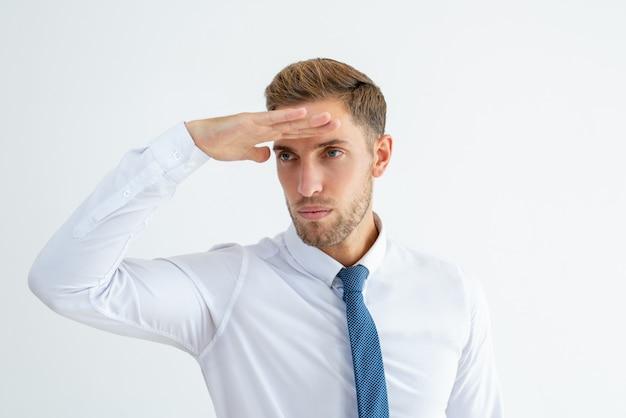 Uomo serio di affari che esamina la distanza