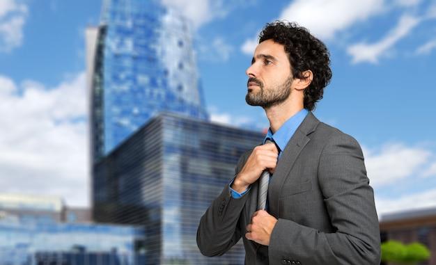 Uomo serio di affari che regola la sua cravatta mentre camminando all'aperto