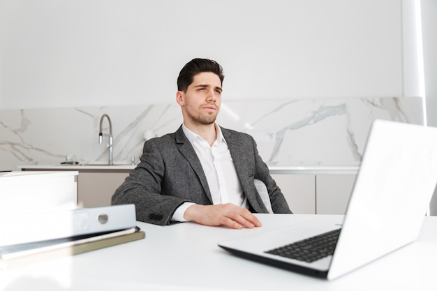Uomo serio di affari che si siede dalla tabella con il computer portatile