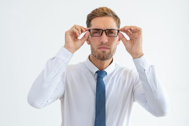 Uomo serio di affari fissando la telecamera attraverso gli occhiali