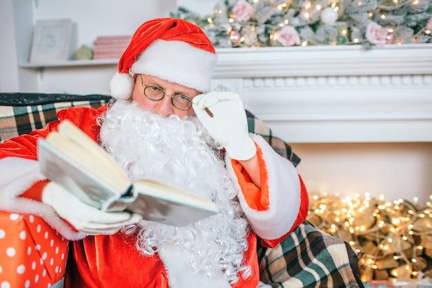 Uomo serio e concentrato in costume di babbo natale legge il libro. tiene la mano sugli occhiali. guy presta attenzione al libro.
