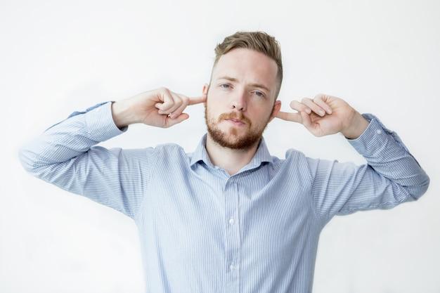 Uomo serio fermare le orecchie con le dita