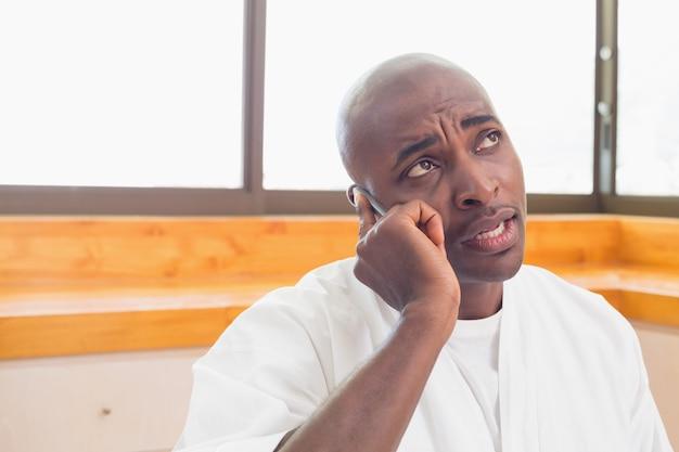 Uomo serio in accappatoio parlando al telefono