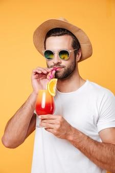 Uomo serio in occhiali da sole bere cocktail