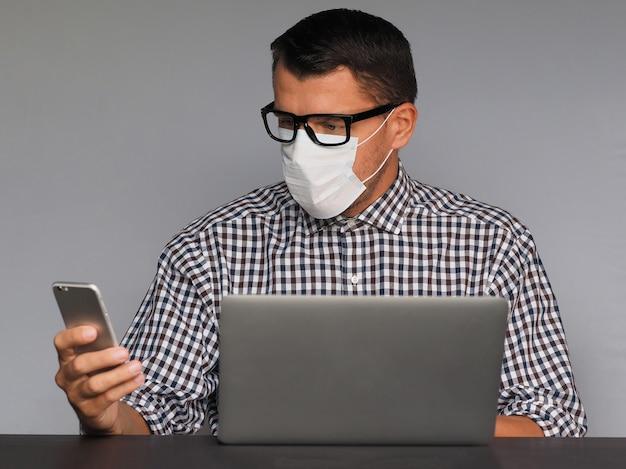 Uomo serio in occhiali e mascherina medica che si siede allo scrittorio davanti al computer portatile e che lavora online sul suo telefono cellulare a casa. quarantine covid-19, pandemia di coronavirus.
