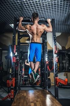 Uomo sexy in palestra con manubri. uomo sportivo con grandi muscoli e un'ampia schiena si allena in palestra, fitness e pressa addominale pompata.