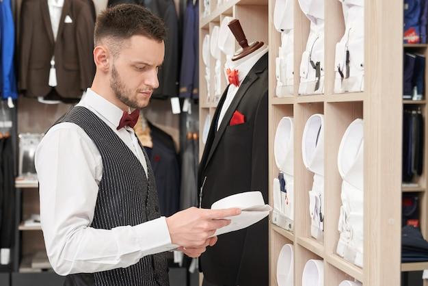 Uomo sicuro barbuto che sceglie camicia in negozio.