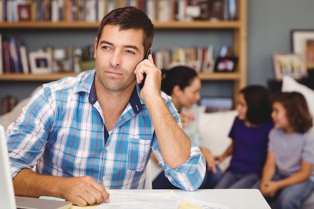 Uomo sicuro che per mezzo del telefono cellulare mentre famiglia