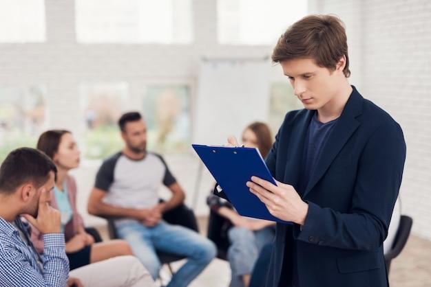 Uomo sicuro con tavoletta blu alla riunione di supporto del gruppo