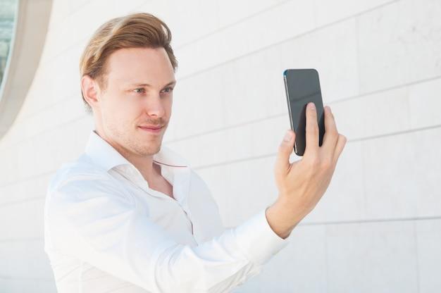Uomo sicuro di affari che posa e che prende la foto del selfie all'aperto