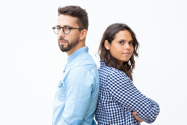 Uomo sicuro e donna in piedi schiena contro schiena
