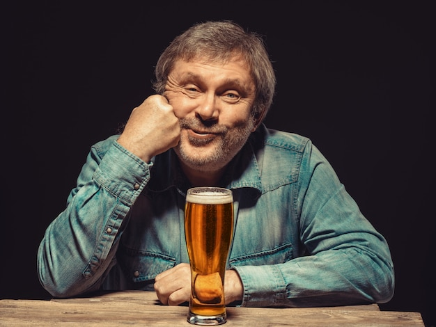 Uomo soddisfatto in camicia di jeans con un bicchiere di birra
