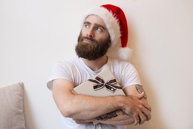 Uomo sognante che indossa il cappello di babbo natale e che abbraccia scatola regalo