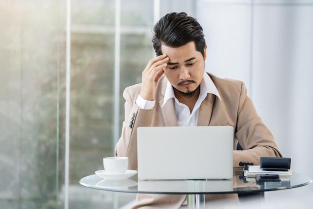 Uomo sollecitato di affari che per mezzo del computer portatile e del problema funzionante