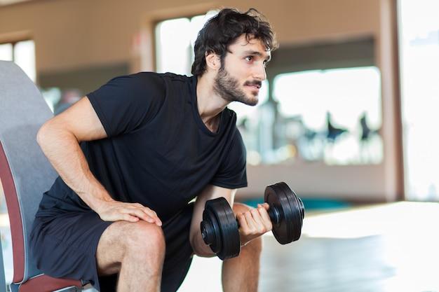 Uomo sollevamento pesi in palestra