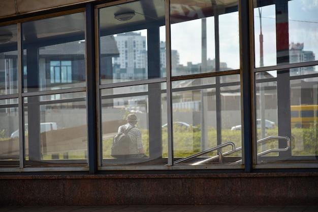 Uomo solo a una fermata dell'autobus in attesa di trasporto pubblico