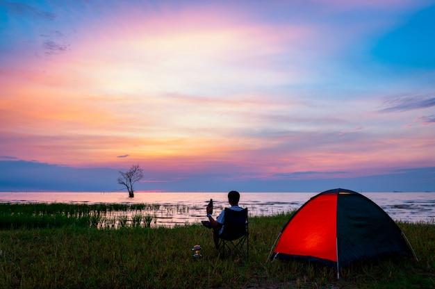Uomo solo che si accampa vicino al lago a pak pak, phatthalung, tailandia