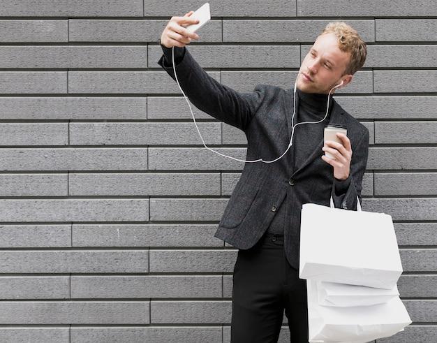 Uomo solo con le cuffie che prendono un selfie
