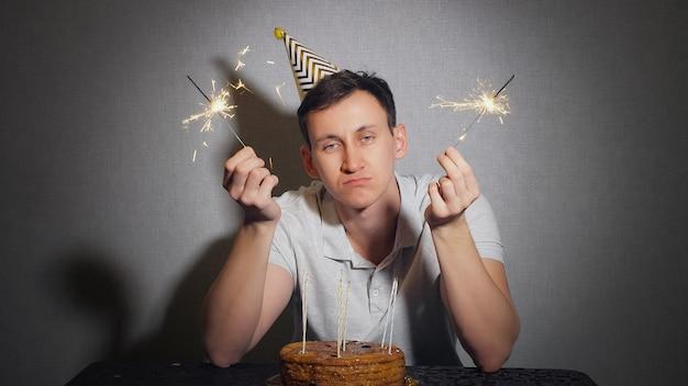 Uomo solo triste in cappello del partito che celebra il compleanno da solo e che tiene la scintillante