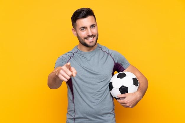 Uomo sopra la parete gialla isolata con pallone da calcio e che punta verso la parte anteriore