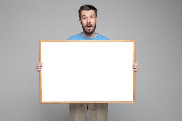 Uomo sorpreso che mostra bordo bianco vuoto