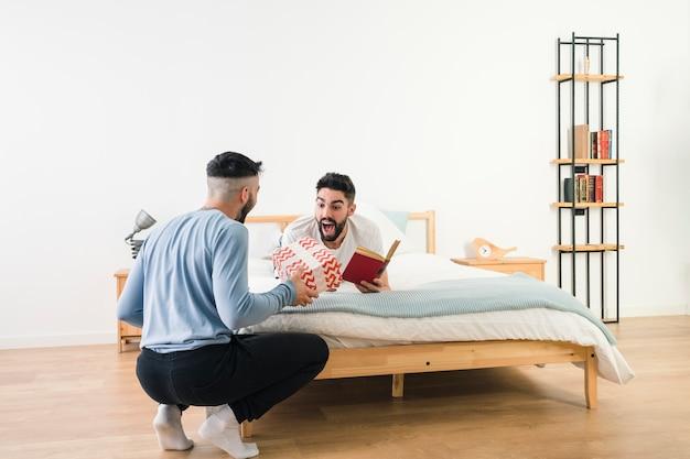 Uomo sorpreso che si trova sul letto che tiene in mano il libro che esamina il suo ragazzo che dà il contenitore di regalo