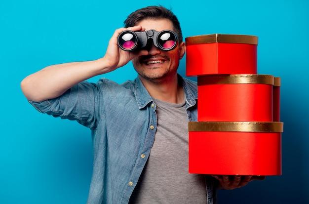 Uomo sorpreso con il binocolo e regali rossi