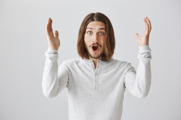 Uomo sorpreso scioccato che alza le mani in alto, trionfante eccitato