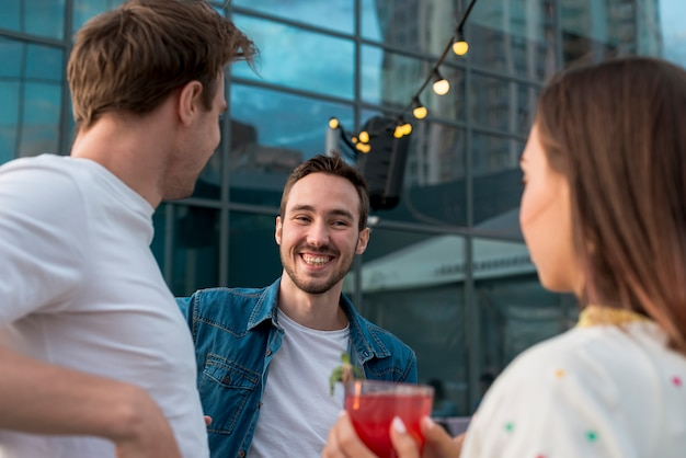 Uomo sorridente accanto agli amici ad una festa