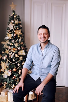 Uomo sorridente affascinante accanto ad un albero di natale
