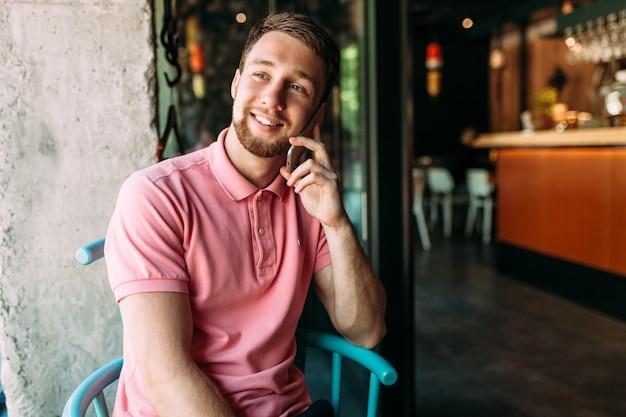 Uomo sorridente bello che si siede in un caffè e che parla sul telefono, pantaloni a vita bassa
