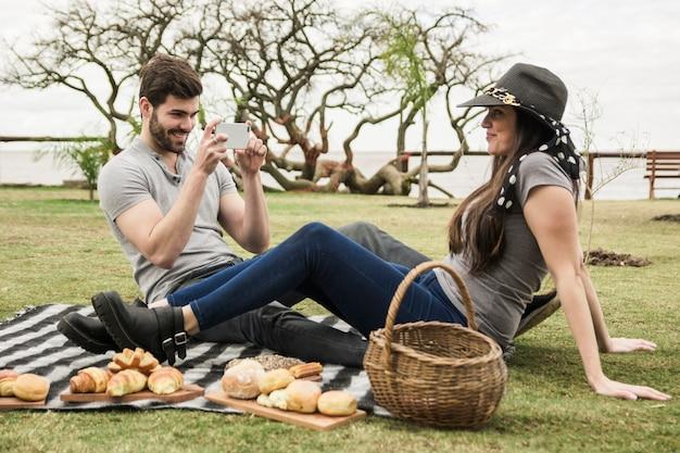 Uomo sorridente che cattura maschera della sua ragazza al picnic nel parco