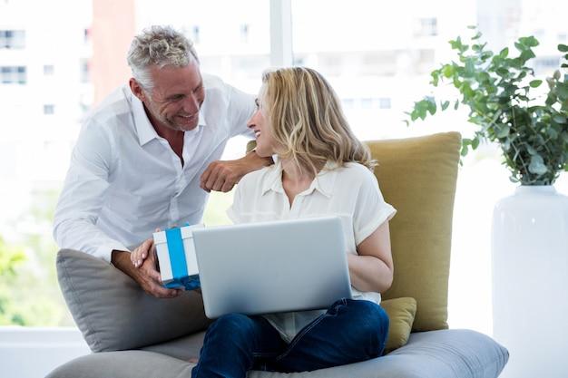 Uomo sorridente che dà regalo al computer portatile della tenuta della donna