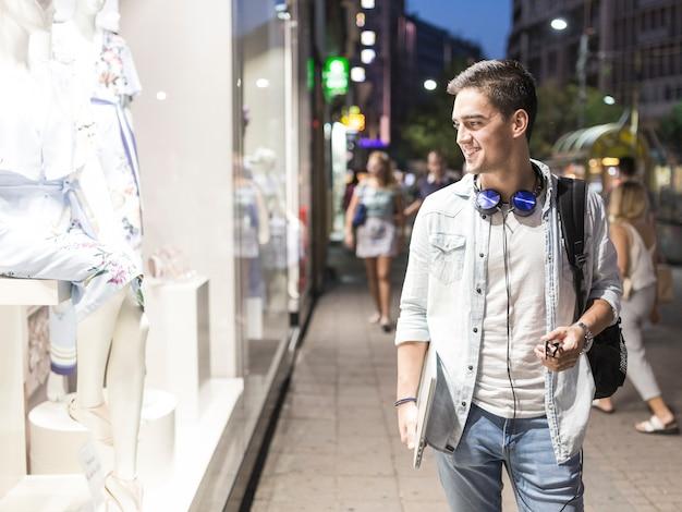 Uomo sorridente che esamina l'esposizione della finestra di un negozio di vestiti