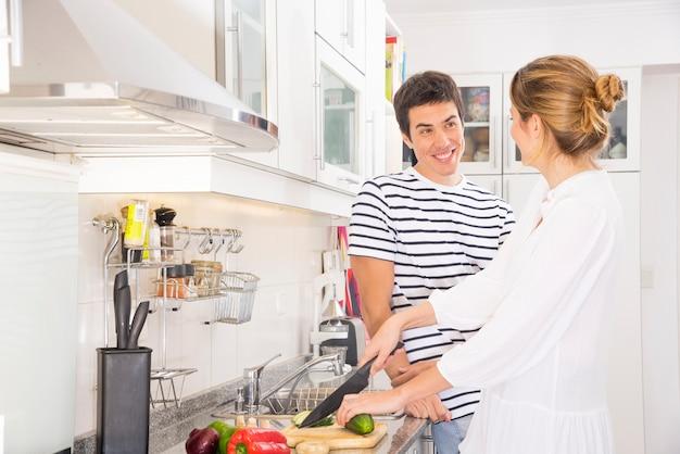 Uomo sorridente che esamina le verdure di taglio della donna con il coltello tagliente