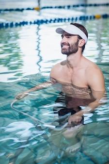 Uomo sorridente che fa bici subacquea in piscina