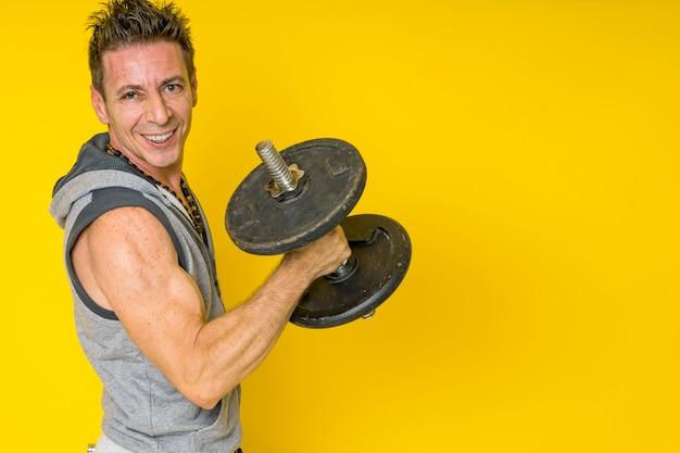 Uomo sorridente che fa bodybuilding con i pesi su una priorità bassa isolata