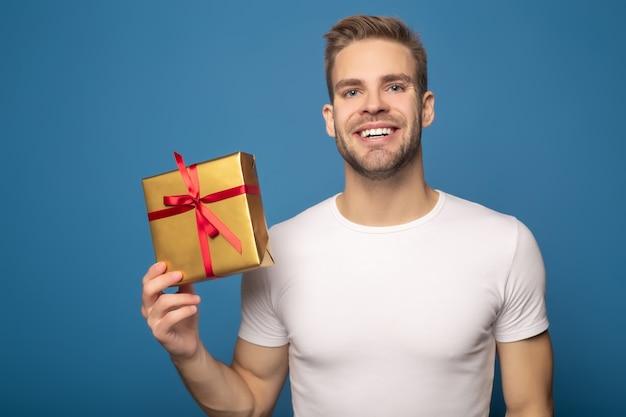 Uomo sorridente che giudica regalo dorato isolato sull'azzurro