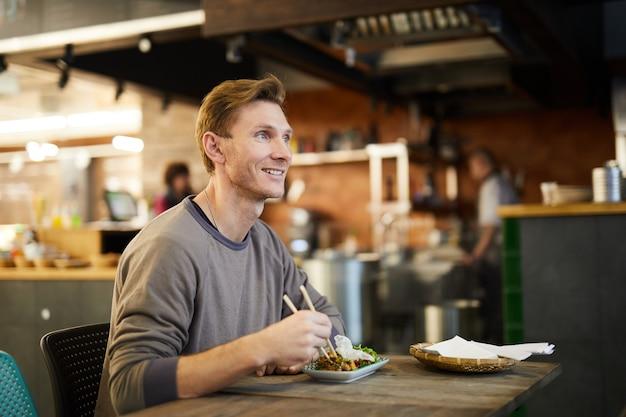 Uomo sorridente che gode del cibo asiatico