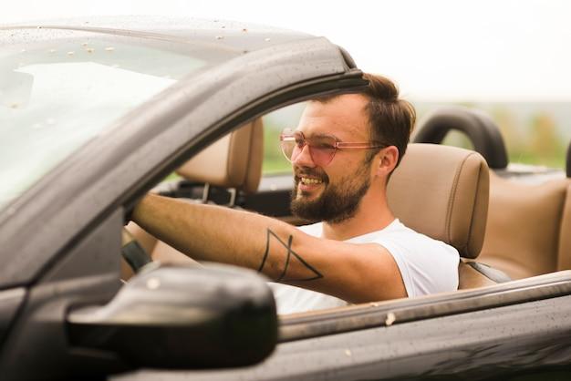 Uomo sorridente che guida un cabriolet