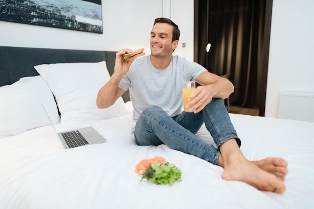 Uomo sorridente che lavora e che gode della prima colazione a letto.