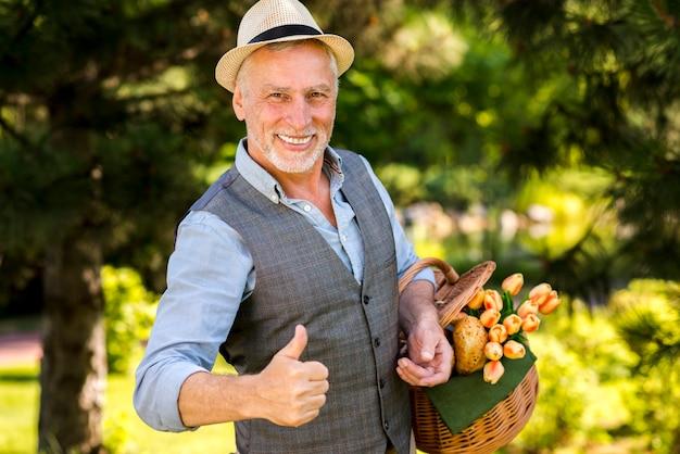 Uomo sorridente che mostra i pollici sul colpo medio