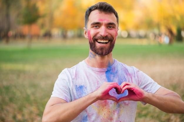 Uomo sorridente che mostra il segno di amore con le mani verniciate