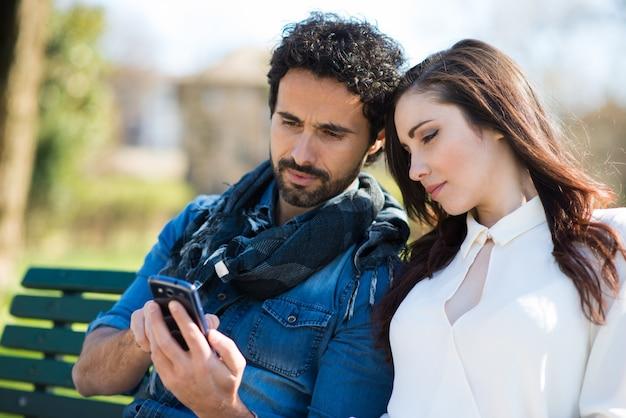Uomo sorridente che mostra il suo telefono cellulare ad una ragazza nel parco