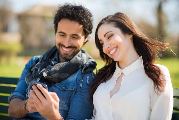 Uomo sorridente che mostra il suo telefono cellulare ad una ragazza