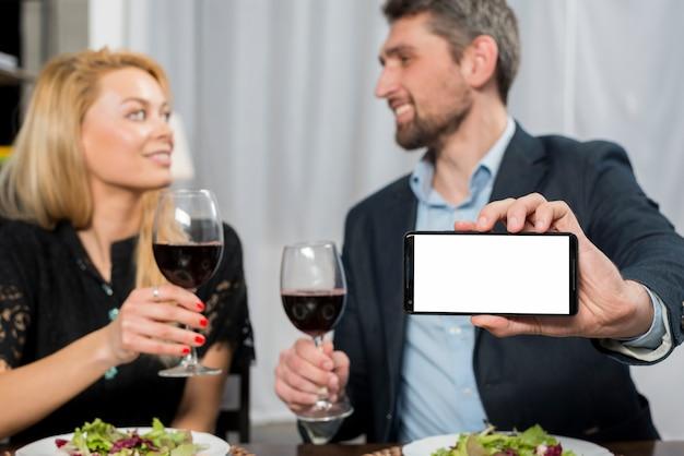Uomo sorridente che mostra smartphone vicino alla donna con bicchieri di vino